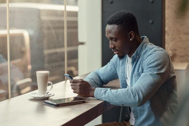 Skoncentrowany czarny przedsiębiorca używa smartfona siedząc w kawiarni z kawą w pobliżu okna.