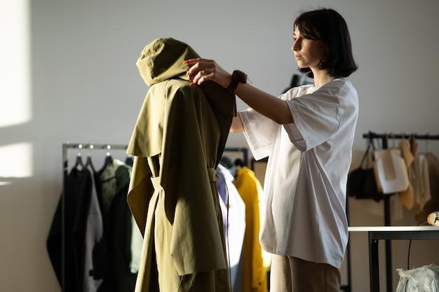 Skoncentrowany designerski płaszcz na manekinie w pracowni projektowej pracownia atelier właściciel szyjący ubrania