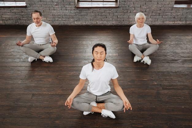Skoncentrowany długowłosy trener w białej koszulce i szarych spodniach skrzyżowanych na nogach, opierając ręce na kolanach siedząc w pozycji jogi
