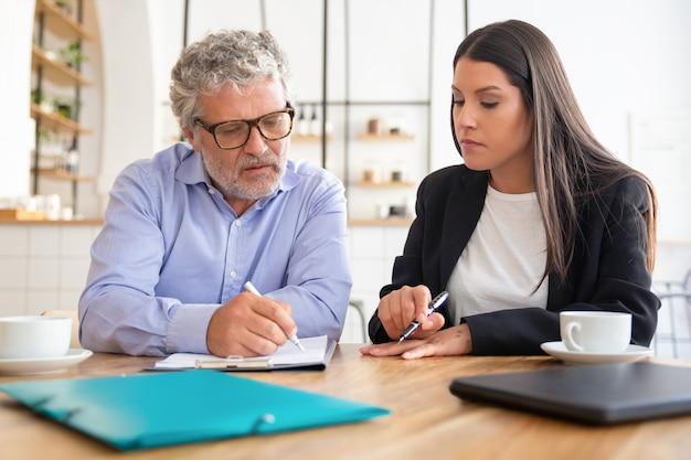 Skoncentrowany dojrzały klient czytający umowę i konsultant na temat szczegółów, wskazując długopisem na kartkę