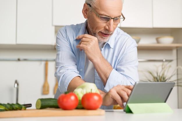 Skoncentrowany dojrzały mężczyzna jest ubranym szkła gotuje sałatki