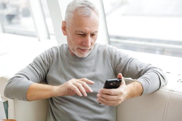 Skoncentrowany dojrzały mężczyzna w swobodnym stroju, piszący na telefonie komórkowym, siedzący w kawiarni w pomieszczeniu