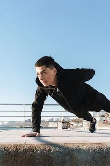 Skoncentrowany dwudziestolatek w czarnym dresie robi pompki na podłodze podczas porannego treningu nad morzem