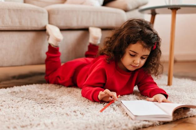 Skoncentrowany dzieciak rysunek w zeszycie. kryty strzał słodkie dziecko leżące na dywanie z piórem.