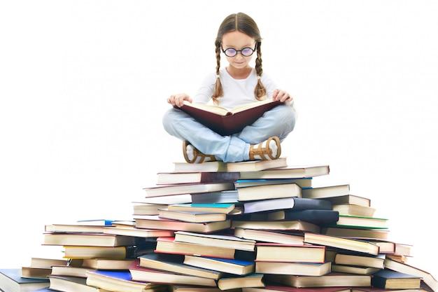 Skoncentrowany dziewczynka otoczona książkami