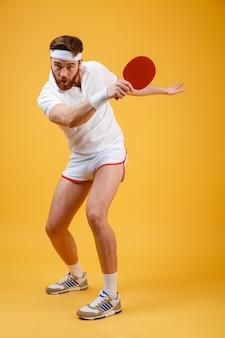 Skoncentrowany emocjonalny młody sportowiec trzyma rakietę do tenisa stołowego.
