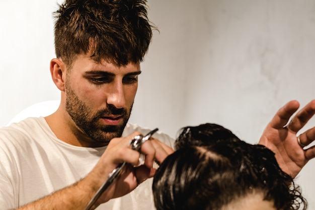 Skoncentrowany fryzjer robi idealne fryzury