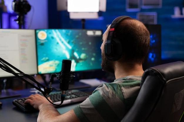 Skoncentrowany gracz grający w strzelankę do wirtualnej rywalizacji przy użyciu profesjonalnych słuchawek. cyber przesyłanie strumieniowe online podczas turniejów gier przy użyciu potężnego komputera z rgb.