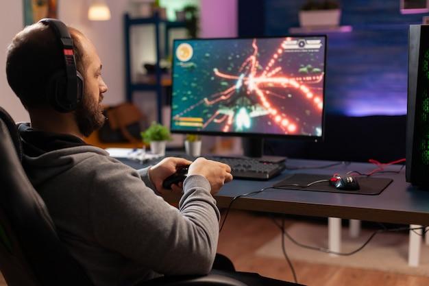 Skoncentrowany gracz grający w wirtualną grę na potężnym komputerze w domu z profesjonalnymi słuchawkami. cyfrowy gracz używający joysticka do rywalizacji w strzelankach kosmicznych późno w nocy w salonie