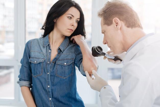 Skoncentrowany inteligentny dermatolog w podeszłym wieku pracujący w szpitalu i umówiony na wizytę u pacjenta podczas wykonywania dermatoskopu do badania skóry