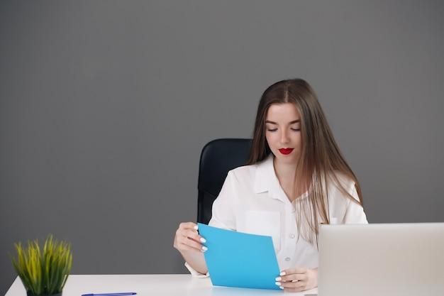 Skoncentrowany inteligentny młody bizneswoman używa swojego komputera w biurze