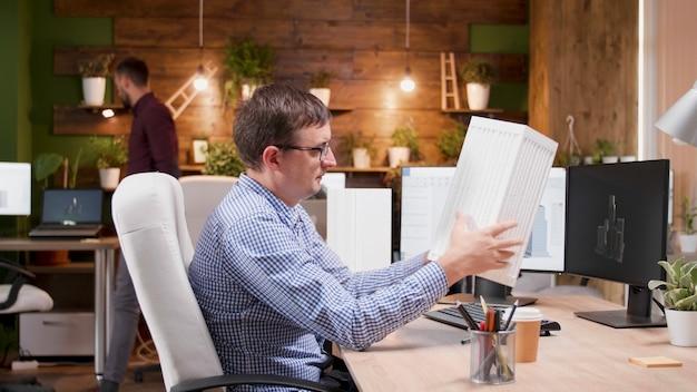 Skoncentrowany inżynier człowiek analizujący prototyp budynku opracowujący konstrukcję techniczną