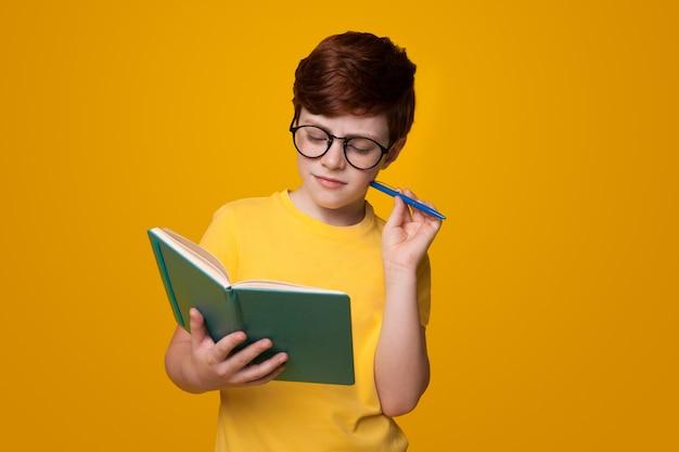 Skoncentrowany kaukaski chłopiec czyta książkę na żółtej ścianie studia, trzymając pióro i nosząc okulary