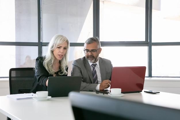 Skoncentrowany kierownik projektu pokazujący prezentację na laptopie współpracownikowi w biurze. skopiuj miejsce. koncepcja pracy zespołowej i komunikacji