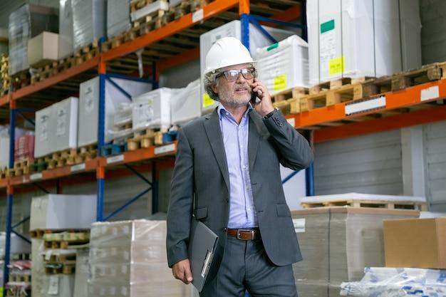 Skoncentrowany kierownik zakładu w kasku, chodzący po magazynie i rozmawiający przez telefon komórkowy