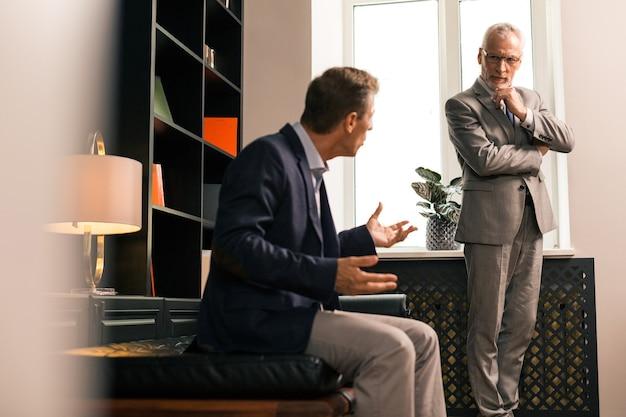 Skoncentrowany lekarz. skoncentrowany starszy psycholog słuchający uważnie pacjenta, stojąc przy oknie i podpierając podbródek