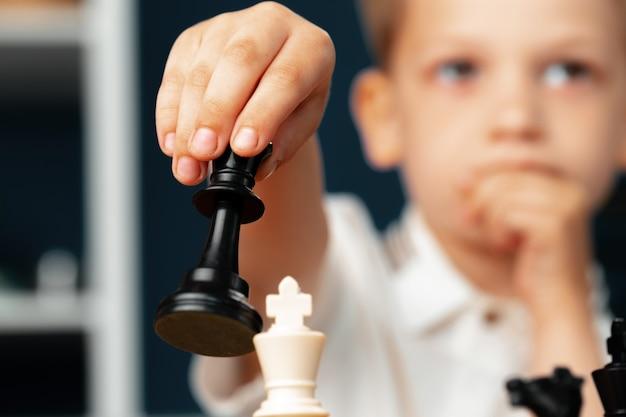 Skoncentrowany mały chłopiec gra w szachy