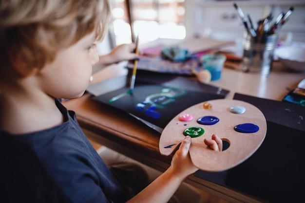 Skoncentrowany mały chłopiec malujący obrazy w domu, w czasie wolnym
