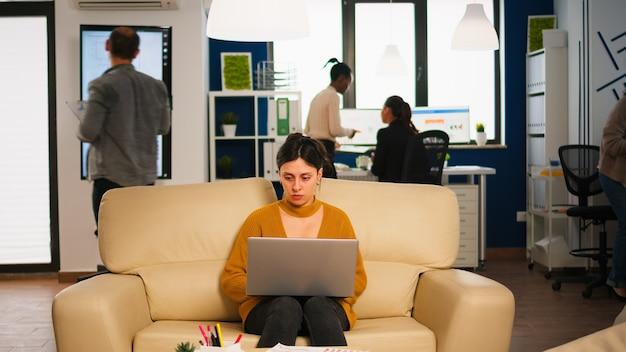Skoncentrowany menedżer czyta maile, pisząc na laptopie, siedząc na kanapie w ruchliwym biurze startowym, podczas gdy zróżnicowany zespół analizuje dane statystyczne w tle. wieloetniczny zespół rozmawia o projekcie