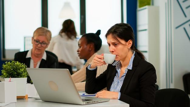 Skoncentrowany menedżer pisania na laptopie siedzący przy biurku w biurze startowym, pijący kawę, podczas gdy różni koledzy pracują w tle. wieloetniczni współpracownicy planujący nowy projekt finansowy.