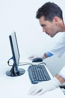 Skoncentrowany męski dentysta patrzeje komputerowego monitoru