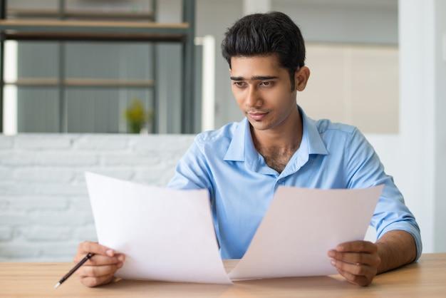 Skoncentrowany męski kierownik uważnie przegląda dokument