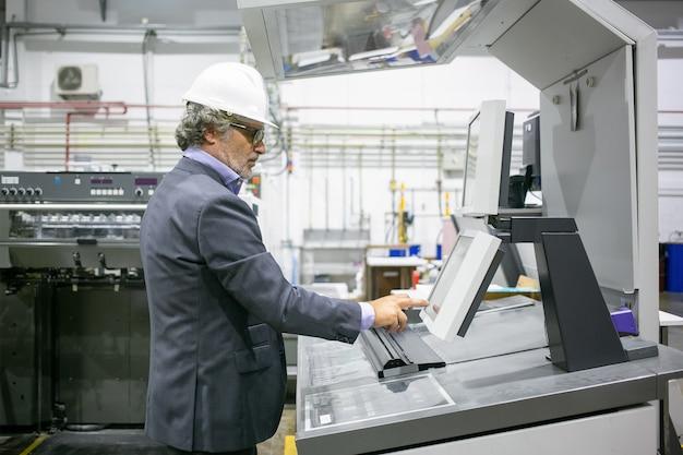 Skoncentrowany męski kierownik zakładu obsługujący maszynę przemysłową, naciskając przyciski na panelu sterowania