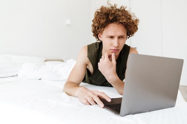Skoncentrowany mężczyzna leży w łóżku w domu za pomocą laptopa