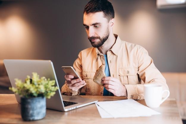 Skoncentrowany mężczyzna przy użyciu swojego telefonu i laptopa