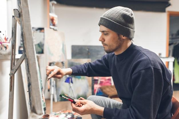 Skoncentrowany mężczyzna stojący w pracowni obok płótna i maluje obraz