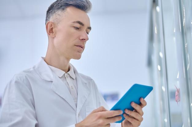 Skoncentrowany mężczyzna studiujący informacje na tablecie