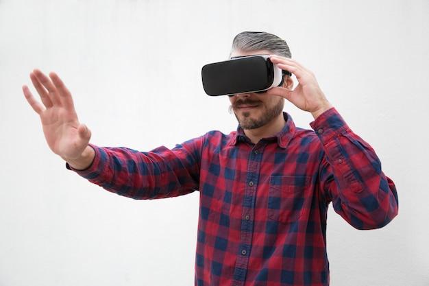 Skoncentrowany mężczyzna za pomocą zestawu słuchawkowego wirtualnej rzeczywistości