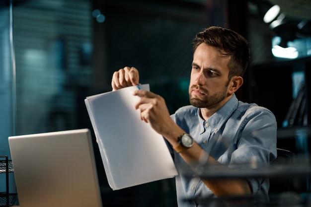 Skoncentrowany mężczyzna zszywa papiery