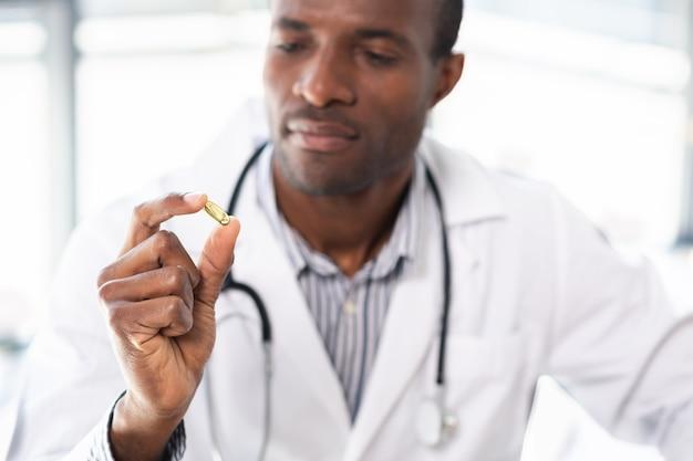 Skoncentrowany międzynarodowy lekarz podnoszący rękę demonstrując witaminę