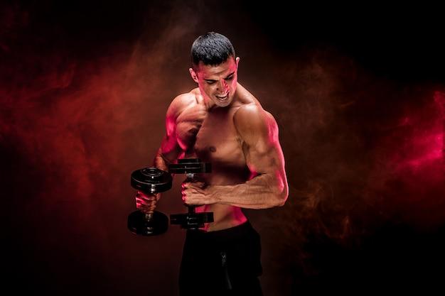 Skoncentrowany mięśniowy mężczyzna robi ćwiczeniu z dumbbell
