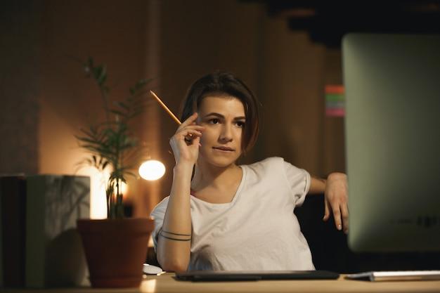 Skoncentrowany młoda dama projektanta mienia ołówek.