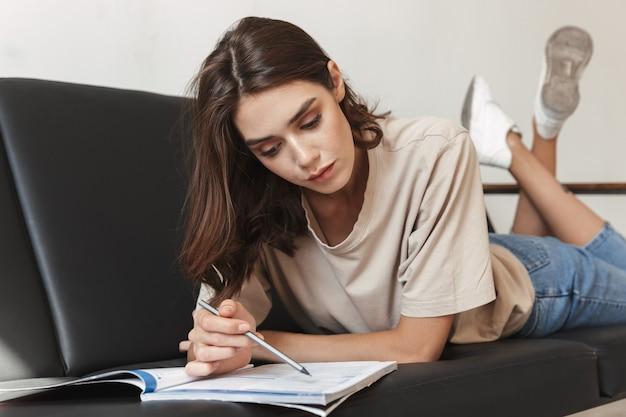 Skoncentrowany młoda piękna kobieta siedzieć w domu w domu na kanapie odrabiania lekcji, studiując pisanie czegoś w zeszycie.
