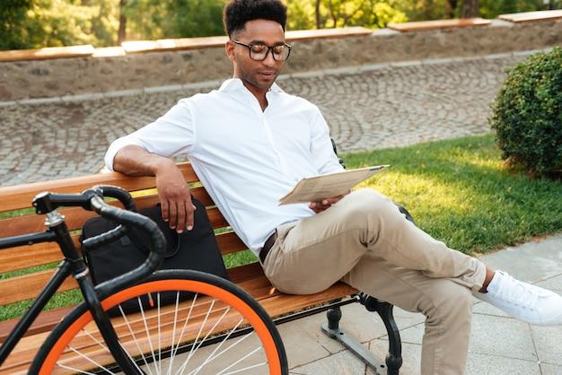 Skoncentrowany młody afrykański mężczyzna czyta gazetę.