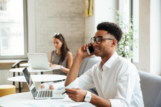 Skoncentrowany młody afrykański mężczyzna siedzi coworking