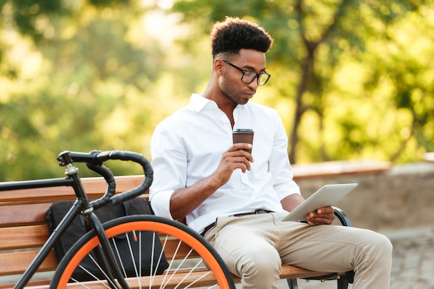 Skoncentrowany młody afrykański mężczyzna używa pastylkę pije kawę.
