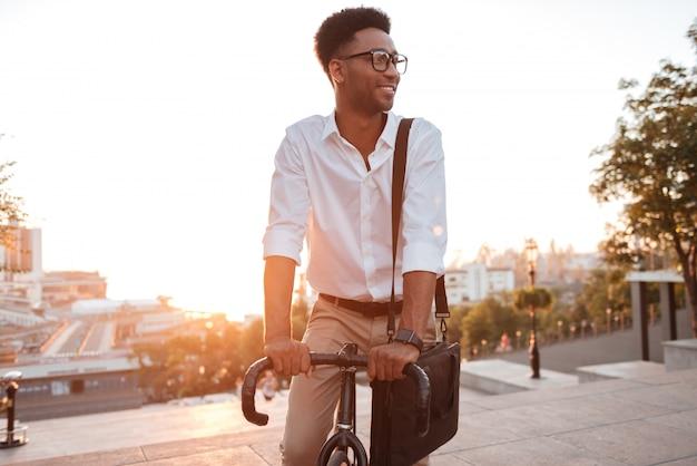 Skoncentrowany młody afrykański mężczyzna w wczesnym poranku z bicyklem