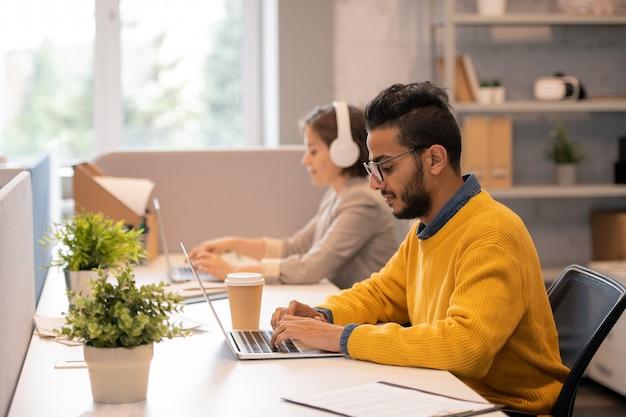 Skoncentrowany młody arabski menadżer z brodą siedzi przy stole z kolegą i korzysta z laptopa podczas pracy nad planem sprzedaży
