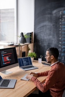 Skoncentrowany młody arabski programista w okularach siedzi przy stole i pisze na klawiaturze wśród trzech komputerów podczas kodowania skryptu