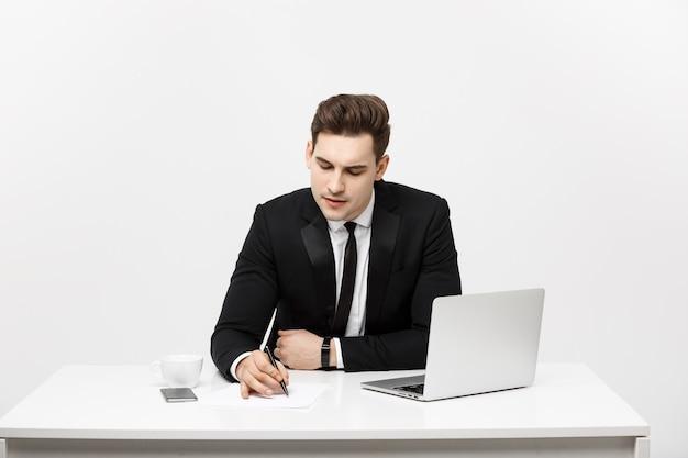 Skoncentrowany młody biznesmen piszący dokumenty przy biurku