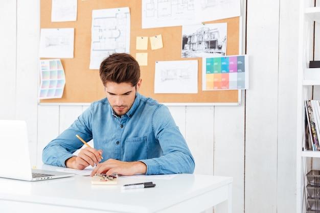 Skoncentrowany młody biznesmen siedzi i pisze przy stole w biurze