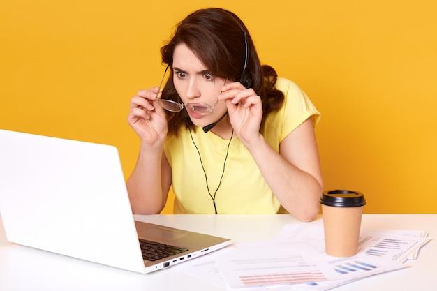 Skoncentrowany młody bizneswoman pracujący na kolanach, opuszcza okulary i przygląda się uważnie na ekranie komputera z zaskoczonym wyrazem twarzy, siedzi przy białym biurku na żółtym tle.
