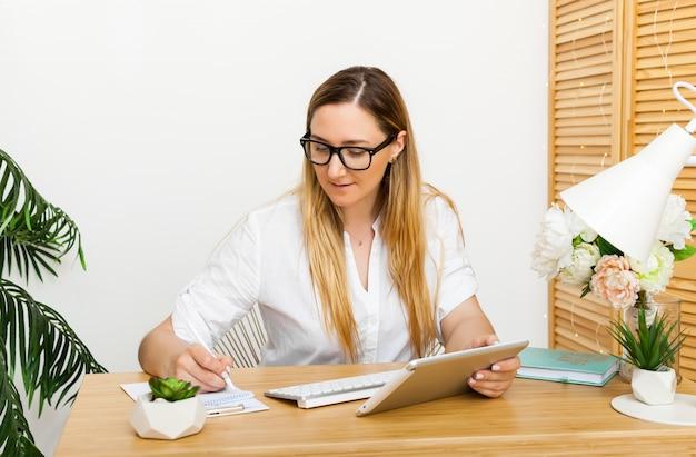 Skoncentrowany młody bizneswoman pracuje na tablecie w jasnym biurze