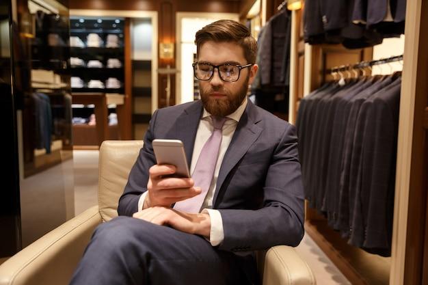 Skoncentrowany młody brodaty biznesmen siedzi w pomieszczeniu gawędzenie