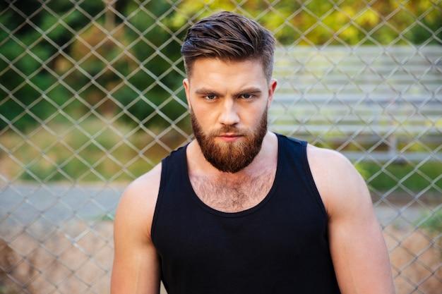 Skoncentrowany młody brodaty mężczyzna w koszulce patrzący na przód na zewnątrz