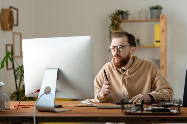 Skoncentrowany młody, brodaty projektant w okularach i bluzie z kapturem siedzi przy biurku i analizuje szkice na komputerze